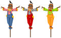 Three scarecrows on wooden sticks Royalty Free Stock Photo