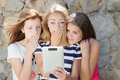 Three scared teen girl friends and tablet computer Royalty Free Stock Photo