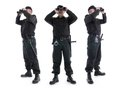 Three security guards wearing black uniform looking binoculars three different directions shot white Stock Photos