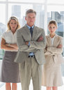 Three serious business people standing together with arms crossed Stock Photography