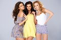 Three sexy chic young women in summer fashion standing arm arm studio background Royalty Free Stock Photos