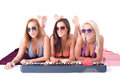 Three sexy girl lying on a towel and playing the synthesizer Royalty Free Stock Image