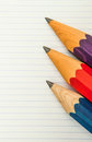 Three sharp thick pencils and lined paper on Stock Photography