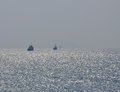 Three ships misty sky sun reflection silhouette sailing on water with foggy weather Stock Photo