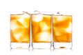 Three shot glass of drink and ice isolated on white Stock Image