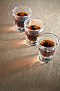 Three shot glasses full of dark colored alcohol Stock Photos