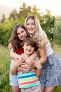 Three siblings hugging in a garden Royalty Free Stock Photo