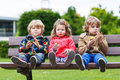 Three siblings sitting on bench and eating chocolate. Royalty Free Stock Photo