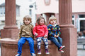 Three siblings sitting together on fountain in city Royalty Free Stock Photo