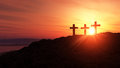 Three silhouetted religious crosses hillside orange sunset background crucifixion concept Royalty Free Stock Image