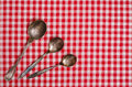 Three silver spoons on a checked table cloth Royalty Free Stock Images