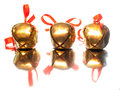 Three sleigh bells with red ribbon bows shiny golden satin in a row on reflective surface Royalty Free Stock Photo