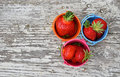 Three small colorful buckets full of strawberry multicolored metal toy red mellow strawberries on old vintage wooden table top Royalty Free Stock Photos