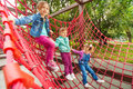 Three small girl sitting on red grid in summer of playground construction Royalty Free Stock Photo