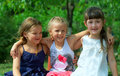 Three small girls embracing in summer park Stock Images