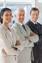 Three smiling business people standing together with their arms folded Stock Photo