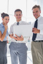 Three smiling business people using a laptop in modern office Stock Photography