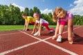 Three smiling children in ready position to run on bending knee marathon summer Stock Photo