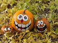 Three Smiling Painted Halloween Pumpkins in a Row Surrounded by Royalty Free Stock Photo