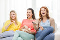 Three smiling teenage girl watching tv at home Royalty Free Stock Photo