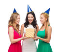 Three smiling women in blue hats with gift box celebration friends bachelorette party birthday concept wearing Royalty Free Stock Photography