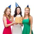 Three smiling women in blue hats with gift box celebration friends bachelorette party birthday concept wearing Royalty Free Stock Photo