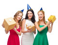 Three smiling women in blue hats with gift boxes celebration friends bachelorette party birthday concept wearing Stock Photos