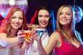 Three smiling women with cocktails and disco ball new year celebration friends bachelorette party birthday concept in evening Royalty Free Stock Images