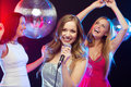 Three smiling women dancing and singing karaoke party new year celebration friends bachelorette party birthday concept in evening Stock Image