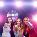 Three smiling women dancing and singing karaoke party new year celebration friends bachelorette party birthday concept in evening Stock Photo