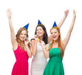 Three smiling women in hats blowing favor horns celebration friends bachelorette party birthday concept wearing blue and and Stock Photos