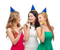 Three smiling women in hats blowing favor horns celebration friends bachelorette party birthday concept wearing blue and Stock Photos