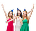 Three smiling women in hats blowing favor horns celebration friends bachelorette party birthday concept wearing blue and and Stock Photography