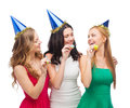Three smiling women in hats blowing favor horns celebration friends bachelorette party birthday concept wearing blue and Stock Photography