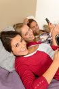 Three smiling young girl lying on bed using smart phones Stock Photography
