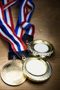 Three sporting event gold medal with red and blue ribbon Royalty Free Stock Photo