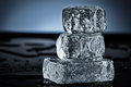 Three stacked ice cubes on black surface Stock Image