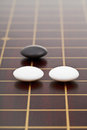 Three stones during go game playing on wooden board close up Royalty Free Stock Photos