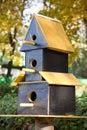 Three storeyed birdhouse funny starling house on autumn park background Stock Photography