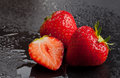Three strawberries on black with water drops Royalty Free Stock Photo