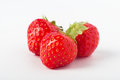 Three strawberries grouped close up of fresh red in a composition at centre of frame with leaves intact Royalty Free Stock Images