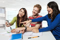 Three students laugh at something on a handphone Royalty Free Stock Photo