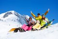 Three students in snow with snowboards happy friends men and women sit lifting and waving hands Stock Photos