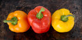 Three sweet peppers orange red and yellow on brown background Stock Images