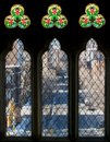 Three tall windows and stained glass Stock Images