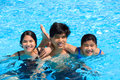 Three teen siblings smiling together in pool Royalty Free Stock Photo