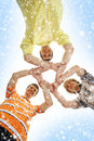 Three teenage boys holding in a form of a star happy caucasian teen modern clothes together the image is taken on blue and snowy Royalty Free Stock Image