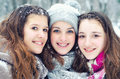 Three teenage girls having fun in the snow on cold winter day Stock Images