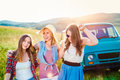 Three teenage hipster girls on a roadtrip summer day young friends outside Royalty Free Stock Image