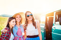 Three teenage hipster girls on a roadtrip summer day young friends outside Stock Photos